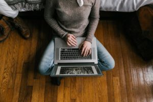 Person in Gray Long Sleeve Shirt Using Macbook Pro