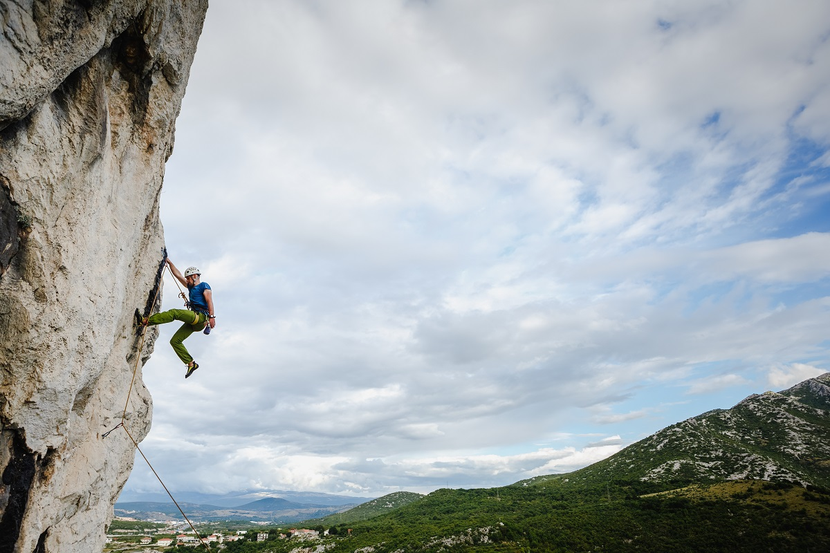A person climbing a rock  Description automatically generated with low confidence